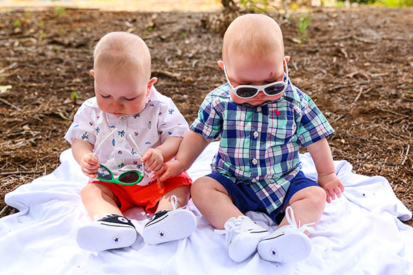 image of twins sitting on blanket with sunglasses