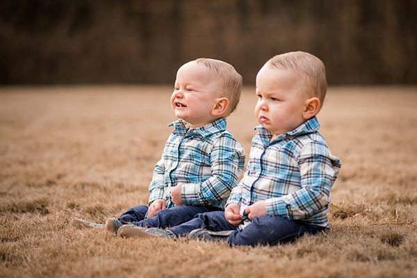 image of twins kneeling in grass