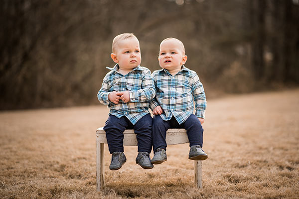 image of twins sitting on bench