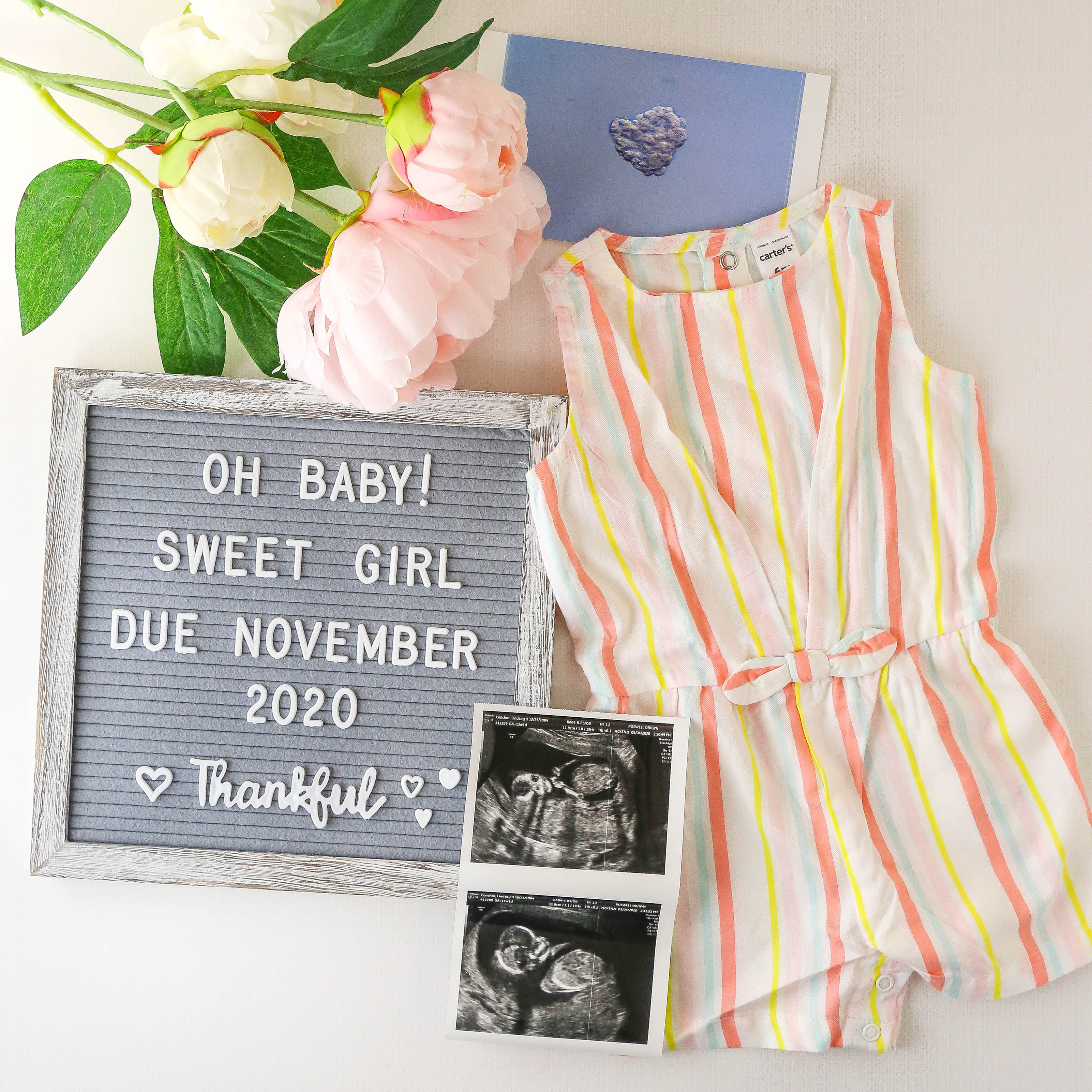 baby annoucement image with flowers, sonogram, baby outfit and letterboard